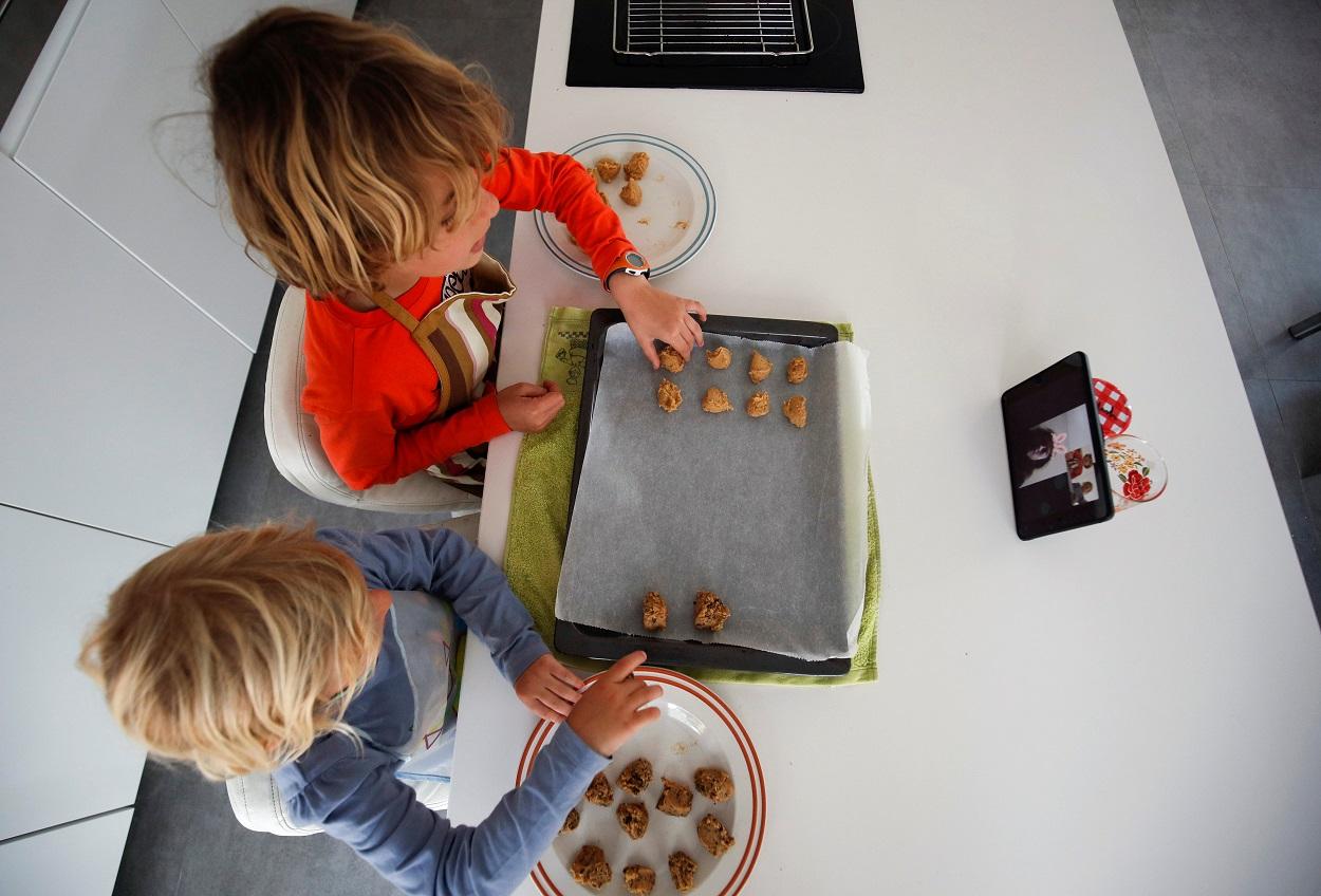 Unos niños preparan unas galletas siguiendo la receta que les dan sus abuelos a través de una tablet. REUTERS/Albert Gea