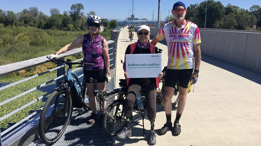 West Sound Cycling Club members on the 520 Trail, posed in front of an adaptive tandem and an ebike