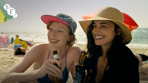 2 people sitting on the beach, one in a baseball cap, the other a sombrero, drinking beers