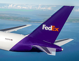 FedEx plane flying over a body of water