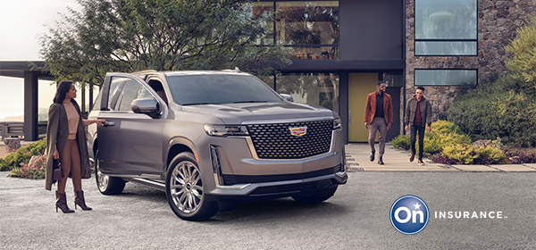 A woman is standing at the passenger door of a Cadillac Escalade while two men walk out of a very modern stone home in the background. OnStar Insurance logo is in the bottom right hand corner of the image