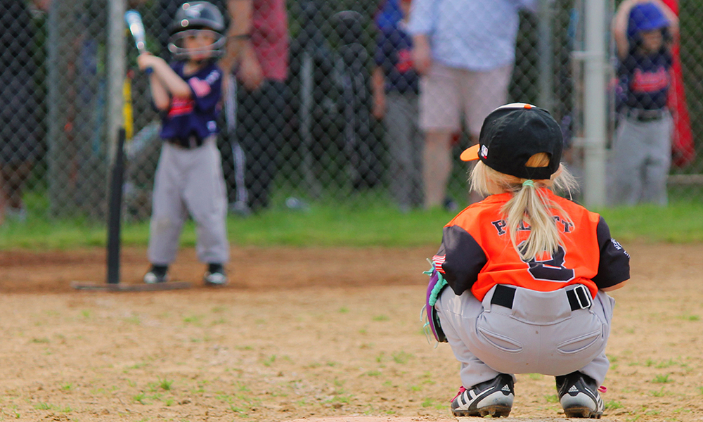 tee ball player squatting in dirt