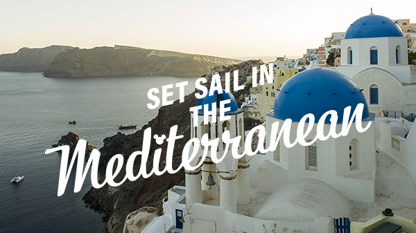 The brilliant blue-domed buildings of Mykonos, Greece rest on the cliffs above the Aegean Sea.