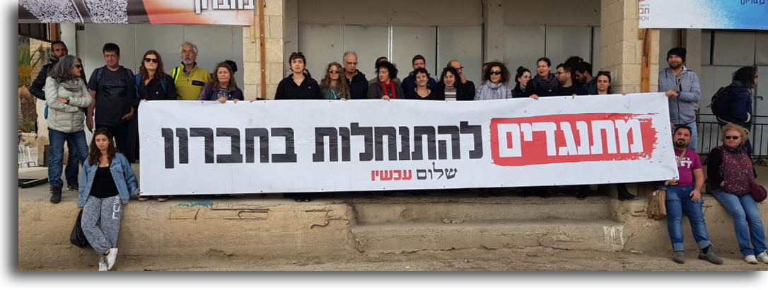 """Image: Peace Now's protest in Hebron from Friday. Sign says: """"Opposing the Settlement in Hebron""""."""