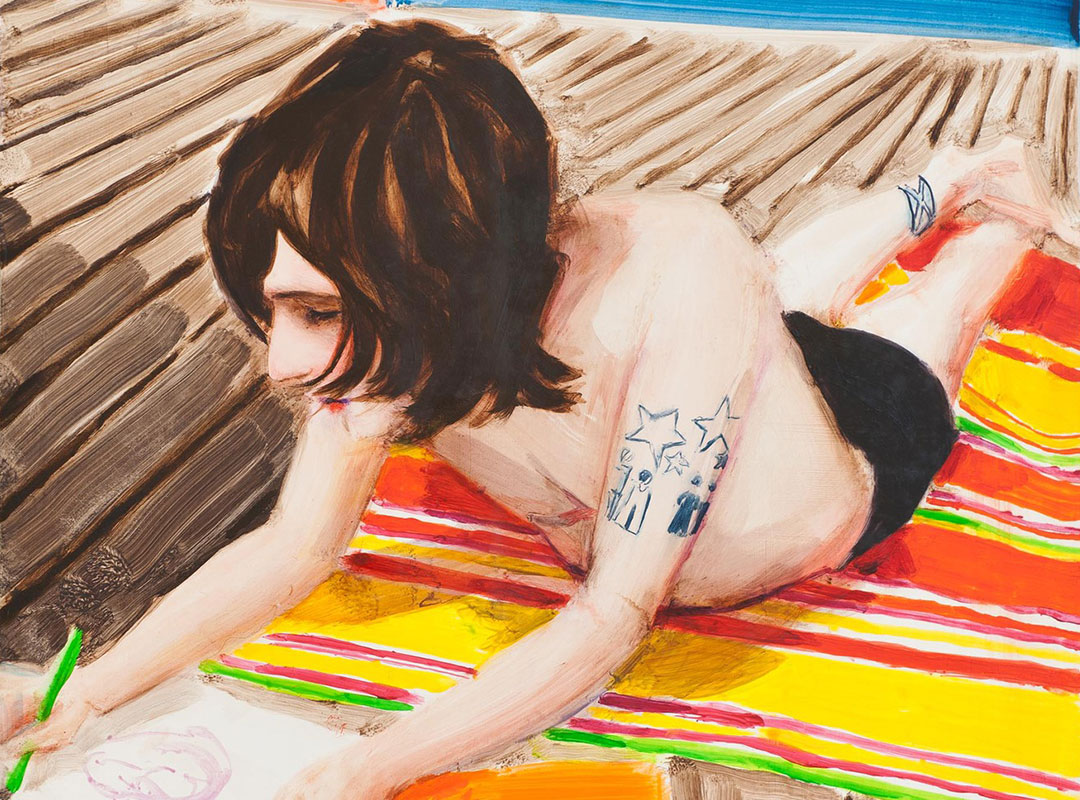 A young man wearing swim trunks lays on his stomach on a beach towel on a wooden boardwalk, drawing on a large piece of paper.