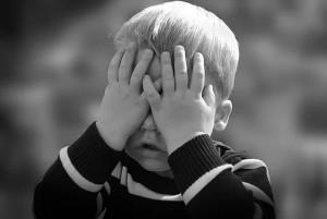 child hiding eyes
