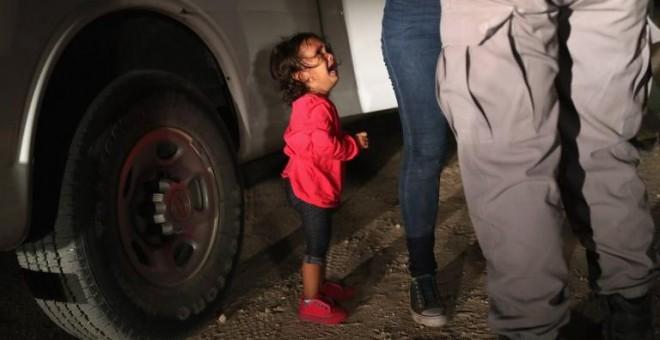 Una solicitante de asilo hondureña de dos años llora mientras su madre es registrada y detenida cerca de la frontera de Estados Unidos y México/AFP