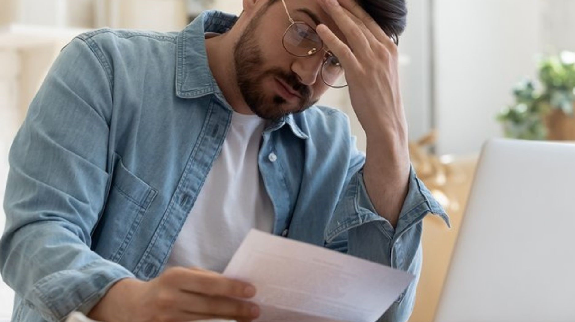 Photo of man looking at paper with hand on head with a stress expression