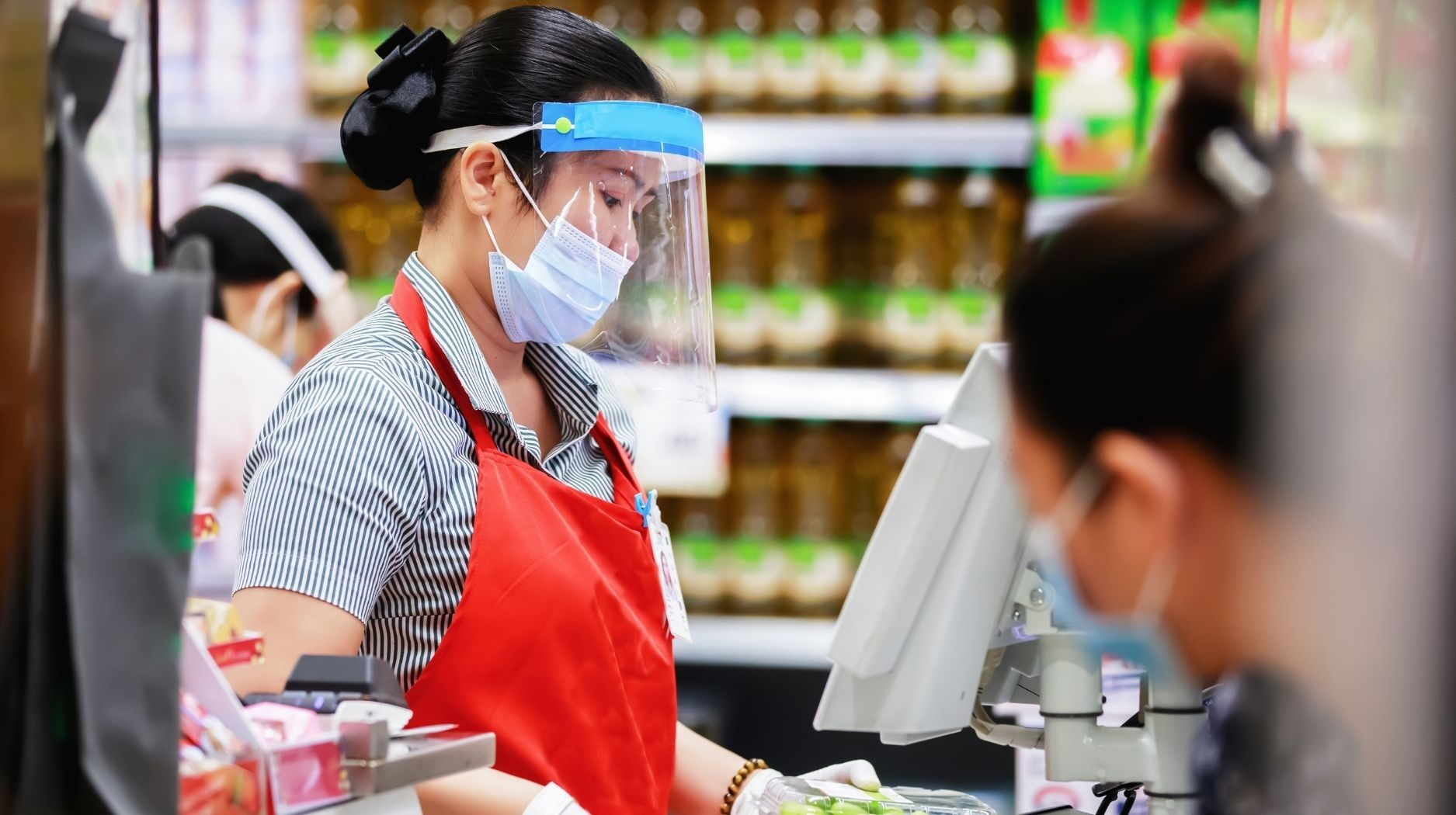 Cashier with face mask and face shield ringing up items