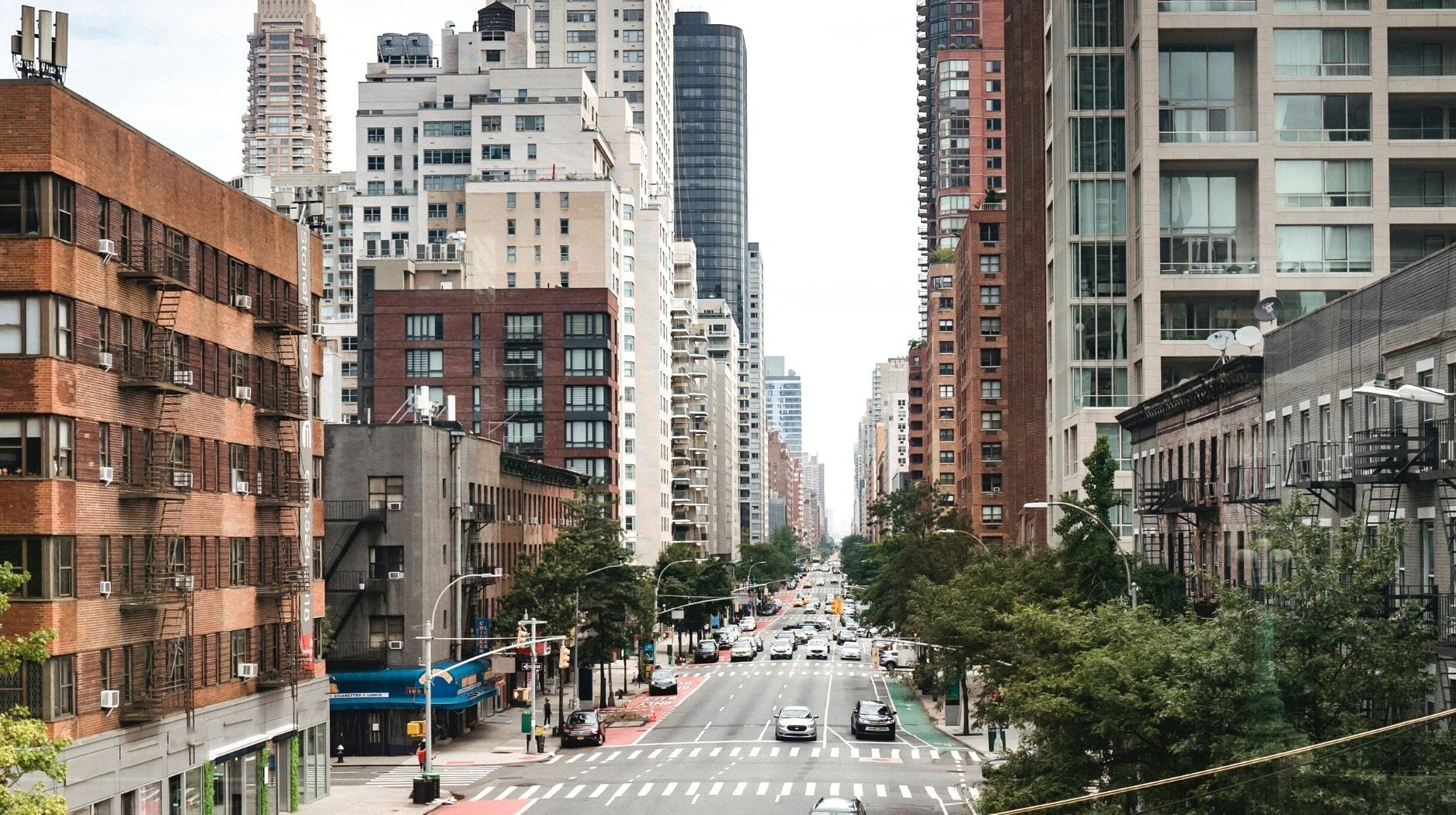Photo of a street in New York City surrounded by high rise buildings and apartments.