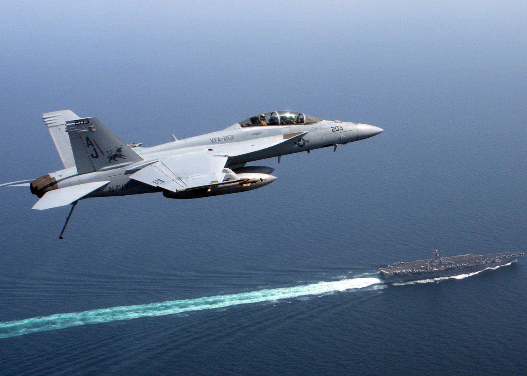 https://americanmilitarynews.com/wp-content/uploads/F-A_18_Super_Hornet_over_USS_Theodore_Roosevelt_CVN_71.jpg