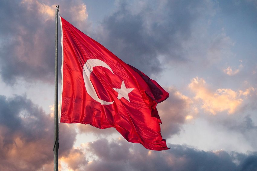 Turkish flag blowing in the wind with clouds in background at sunset
