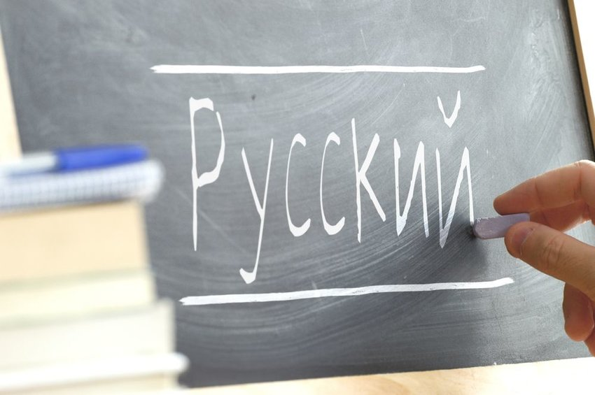 Person writing Russian on a board with chalk