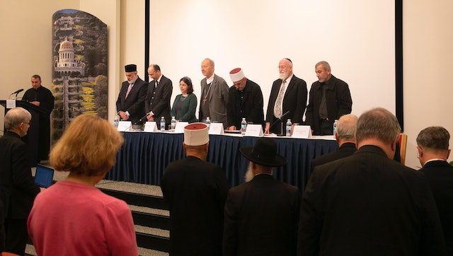 Father Yousef Yakoub (left) recited the Prayer of St. Francis of Assisi in Arabic, English, and Hebrew as audience members and fellow panelists (from left) Emir Muhammad Sharif Odeh, Baha'i International Community Deputy Secretary-General Shervin Setareh, Rabbi Naama Dafni-Kelen, Bishop Michel Dubost, Sheikh Jaber Mansour, Rabbi David Metzger, and Sheikh Rashad Abo Alhigaa stood in reverence.