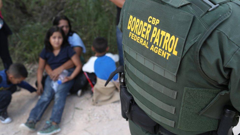Solicitantes de asilo procedentes de América Central esperan a que la guardia fronteriza les traslade a un centro de acogida.