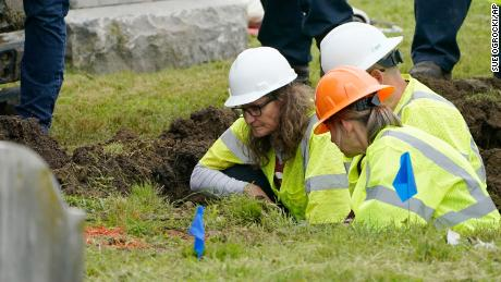 Oklahoma state archaeologist Kary Stackelbeck, left, examines the digging site as excavation begins at Oaklawn Cemetery in a search for victims of the Tulsa Race Massacre believed to be buried in a mass grave, Tuesday, June 1, 2021, in Tulsa, Okla. (AP Photo/Sue Ogrocki)