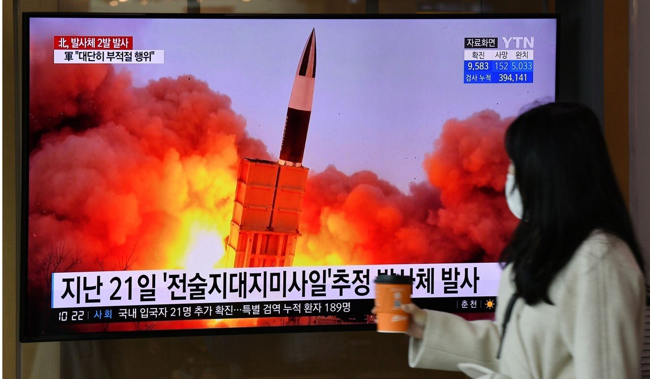 A woman walks past a screen showing file footage of a North Korean missile test, at a railway station in Seoul on March 29. Photo: AFP