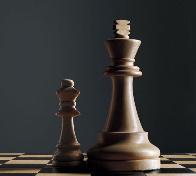 Chess king piece casting a shadow on a distant Queen piece