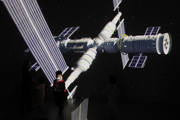 A child stands near a giant screen showing the images of the Tianhe space station at an exhibition featuring the development of China's space exploration on the country's Space Day at China Science and Technology Museum in Beijing, China April 24, 2021.