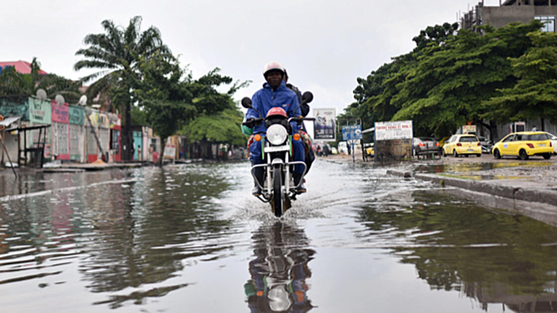 Motorcylce on flooded road in DRC