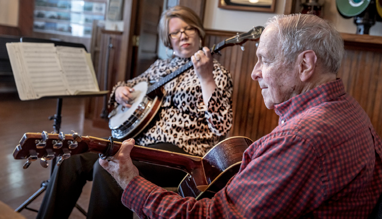Two people playing instruments inside