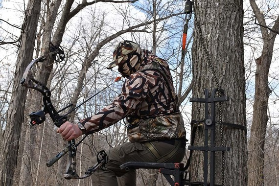 Archer wearing harness in tree stand
