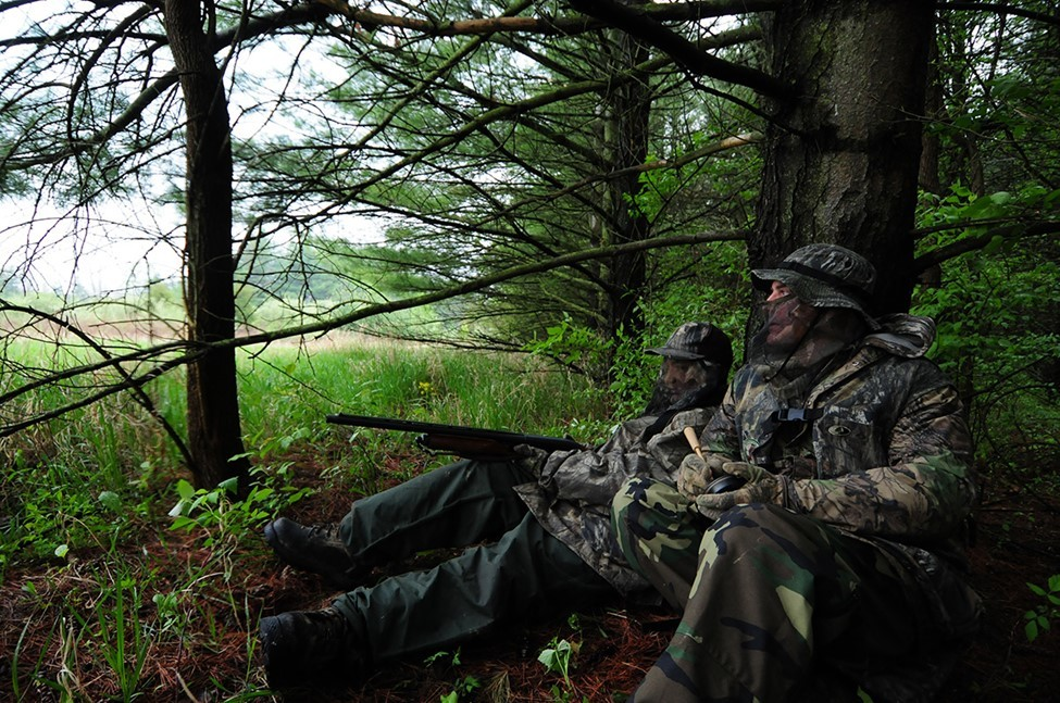 Turkey hunters camouflaged in the woods