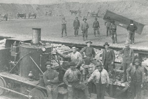 black and white historic photo of men standing in front of the locomotive
