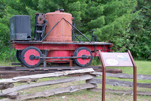 An old steam locomotive sits on an outdoor platform. An interpretive sign is in front of it.