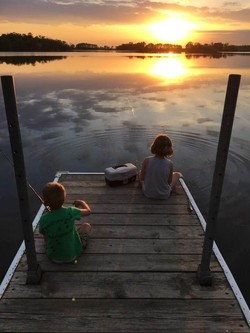 two kids fishing off the dock with a sunset