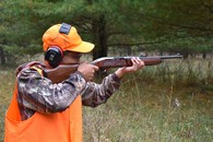 hunter dressed in blaze orange with ear protection