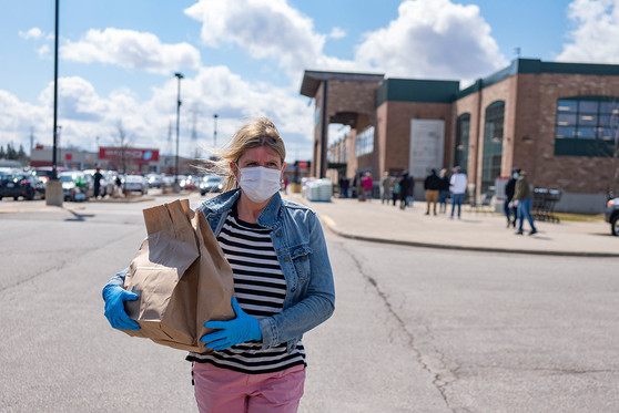 A woman wearing a face mask as protection against COVID-19 walks back to her car with a bag of groceries.