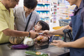 A family uses a SNAP electronic benefits transfer card to purchase food at a grocery store.