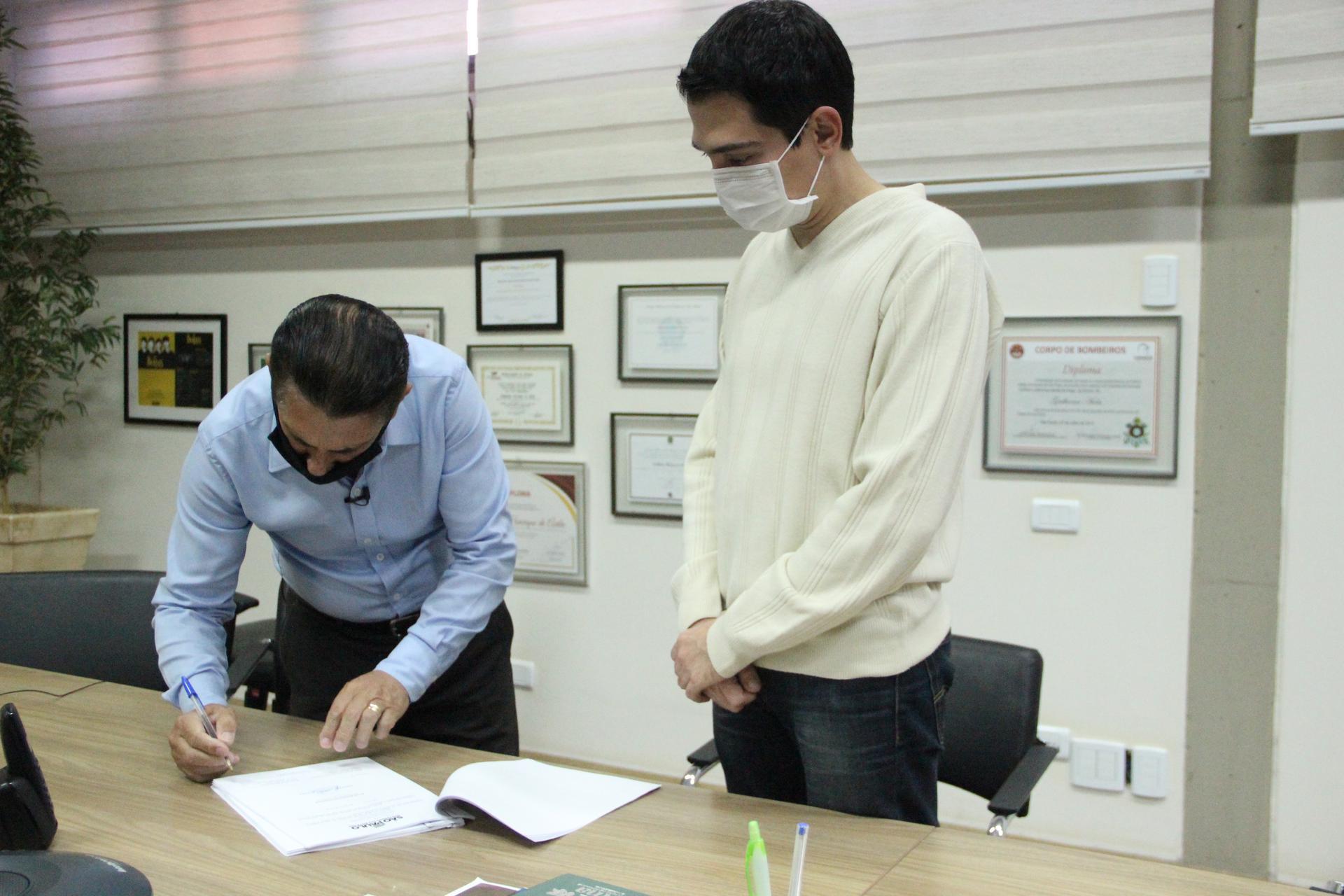 Deputado Sebastião Santos assinando ao lado do prefeito de Barretos, Guilherme Ávila