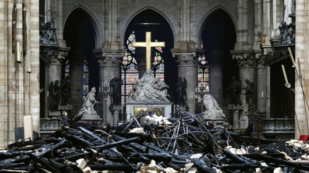 Entre humo y escombros se aprecia la cruz, que sobrevivió al incendio. / AFP
