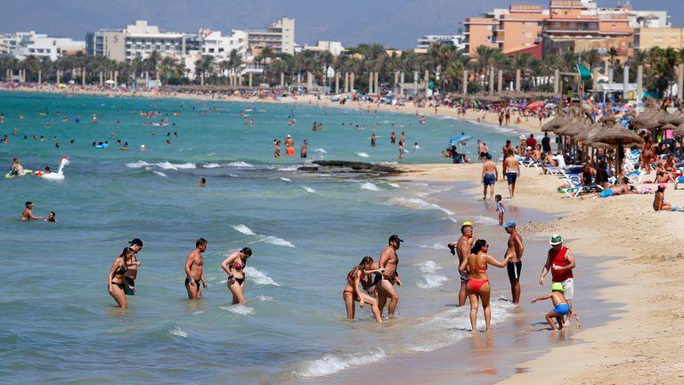 People sunbathe and swim on El Arenal beach in Palma de Mallorca