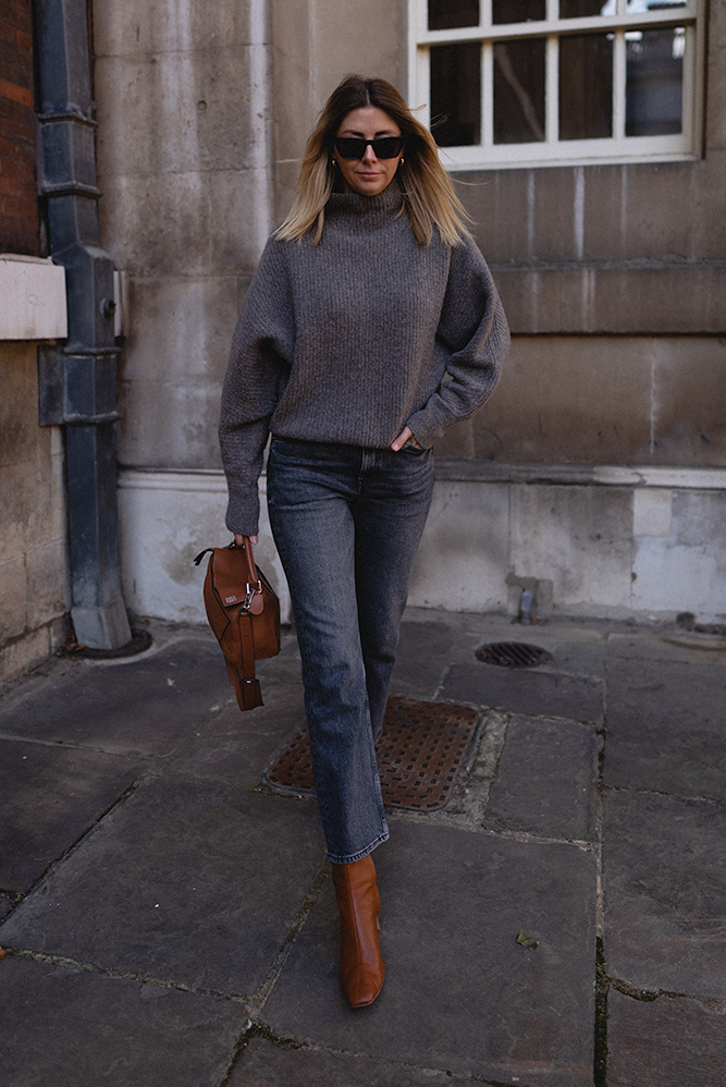 Emma Hill Autumn style. Tan leather small Loewe Puzzle bag, grey ribbed chunky knit jumper, cropped washed black jeans, tan leather square toe ankle boots, Le Specs cat eye sunglasses. Chic autumn outfit