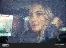 Image result for picture of a person sitting looking out a window at it raining