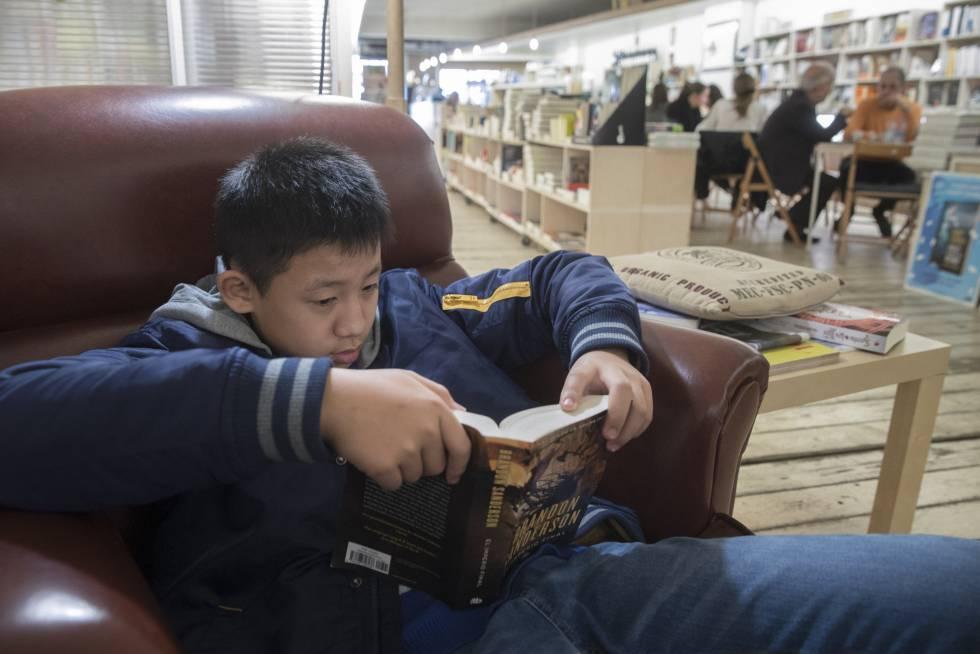 Hao Yu, de 12 años, lee un libro en la librería +Bernat, en Barcelona.