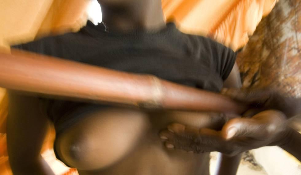 Salamatou, un sanador, plancha con su bastón los pechos de una de las jóvenes de su aldea en Ombessa, Camerún, en el año 2007.