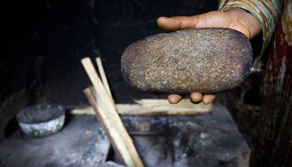 Philomena, de 39 años, usó esta piedra calentada al horno para planchar los pechos de sus hijas. Imagen tomada en Yaundé, Camerún, en 2007.