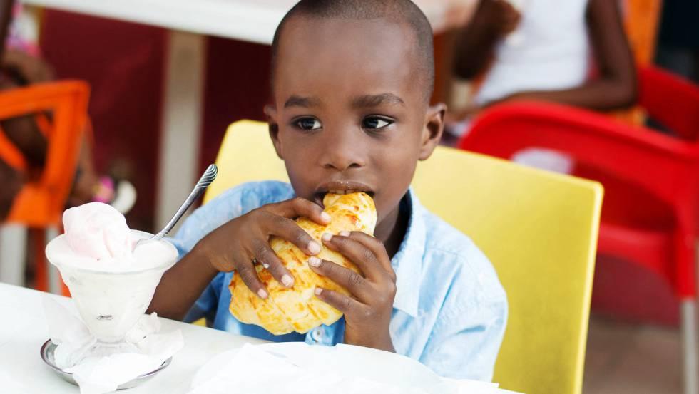 Un niño desayunando un bollo en Costa de Marfil.