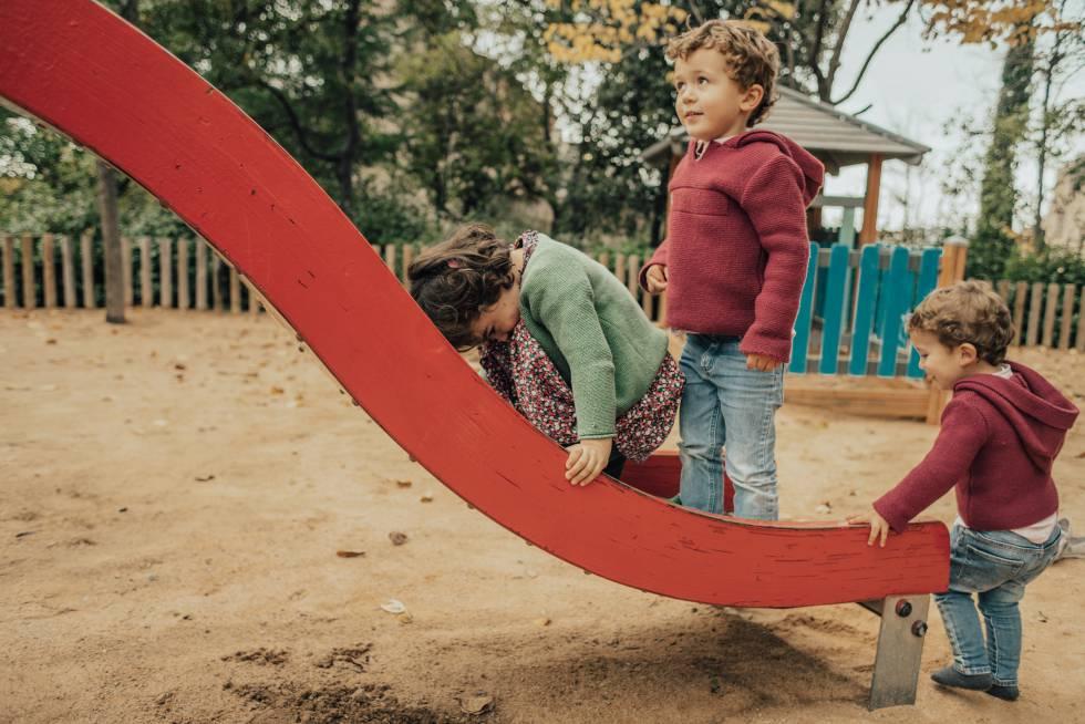Tres niños juegan en el parque.
