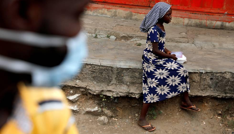 Una niña se dispone a comer en una acera después de haber recibido una ración de alimento de un grupo de voluntarios que distribuye comida a personas sin hogar en Accra, Ghana, el 4 de abril de 2020.