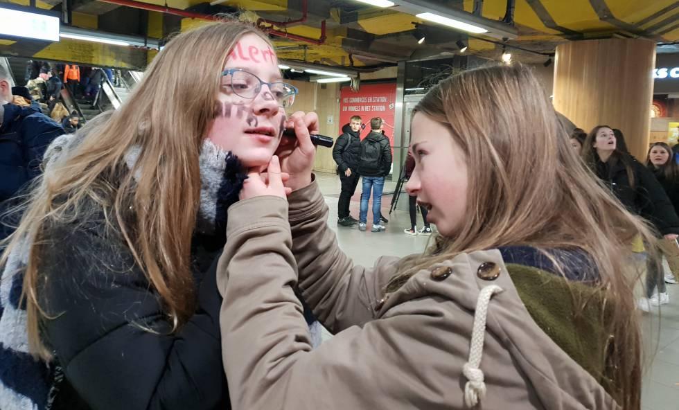 Una alumna pinta la cara de una compañera rumbo a una de las protestas en Bruselas.