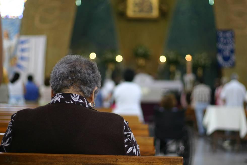 Una mujer reza sentada en un banco de una Iglesia católica.