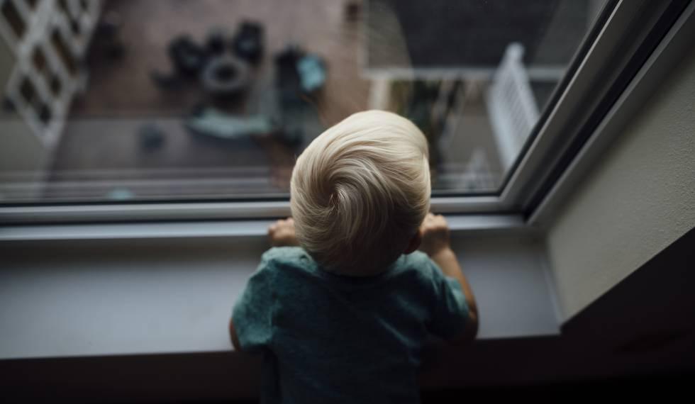 Un bebé mira por una ventana.