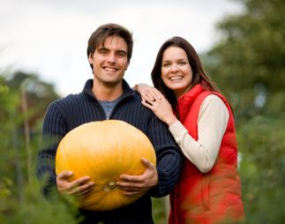Young smiling couple standing on allotment holding large pumpkin smiling at camera