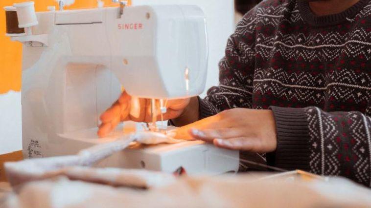Black man using sewing machine garment construction