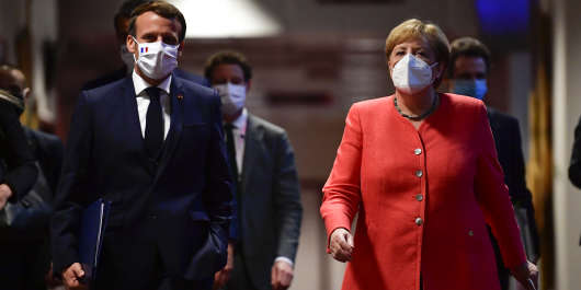 German Chancellor Angela Merkel (R) and French President Emmanuel Macron (L) arrive for a joint press conference at the end of the European summit at the EU headquarters in Brussels on July 21, 2020. - EU leaders approved a 750-billion-euro package to revive their coronavirus-ravaged economies after a tough 90-hour summit on July 21, along with a trillion-euro budget for the next seven years. (Photo by JOHN THYS / POOL / AFP)